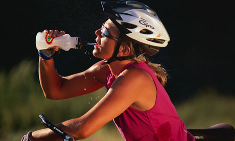 Woman cyclist indulging in water during warm ride.