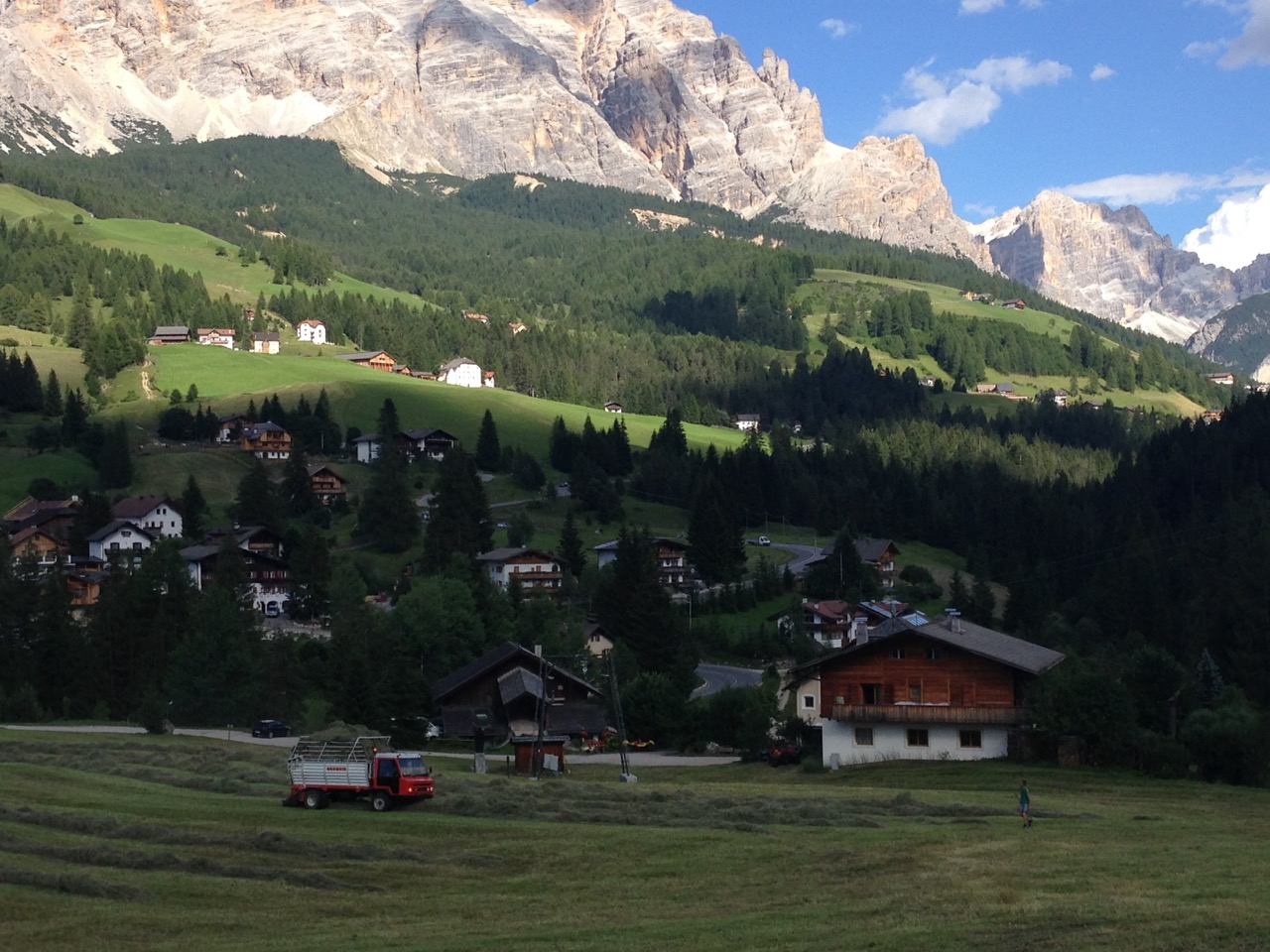 Picture of the Dolomites farmer working in field with mountains in background