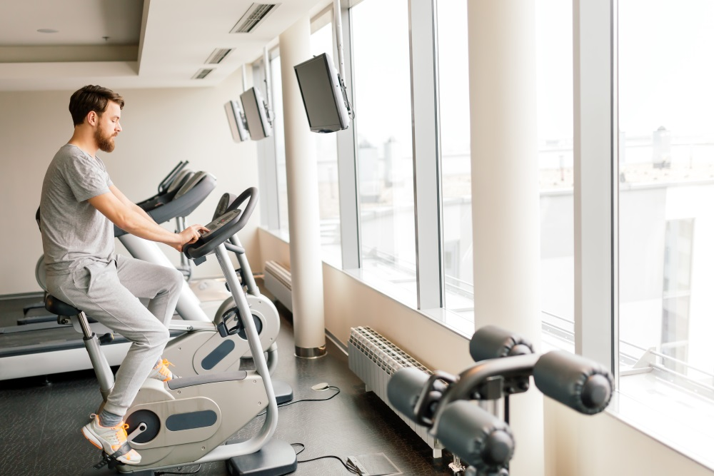 Sportive male exercising on bicycle in gym